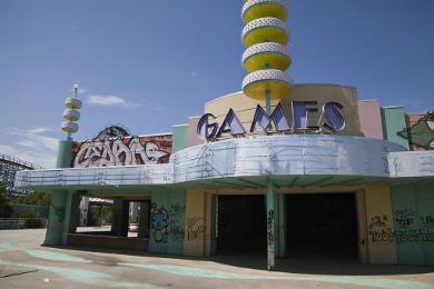 Das Bild zeigt einen älteren Vergnügungspark mit Graffiti an den Wänden und einem Schriftzug GAMES.