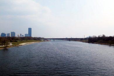 Das Bild zeigt die Donau in Wien, eine Brücke und Hochhäuser im Hintergrund.